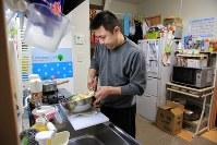 仮設住宅で仕込みをする後藤さん。「こんな小さいキッチンも使い方を考えたら、喜んでもらえる料理が作れるんですよ」=宮城県南三陸町で2014年11月11日、梅村直承撮影