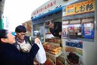 「しお彩号」の最後の日となった「南三陸・復興市」。常連客が次々と惣菜を求めて、午前中に全てが売り切れた。津波で壊された「しお彩」の写真(手前)も車体に貼られていた=宮城県南三陸町で2016年12月29日、梅村直承撮影