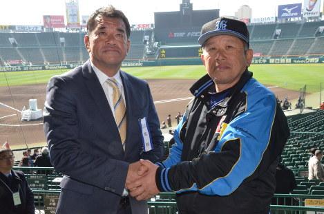 健闘を誓って握手する至学館の麻王義之監督(左)と呉の中村信彦監督=阪神甲子園球場で