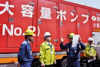 重大事故対策資機材置き場で関西電力の説明を受ける三日月・滋賀県知事(左から2人目)=福井県おおい町の大飯原発で、塚原和俊撮影