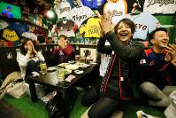 WBC準決勝をテレビで観戦し、菊池の同点本塁打に盛り上がる人たち=東京都千代田区で22日午後0時3分、森田剛史撮影
