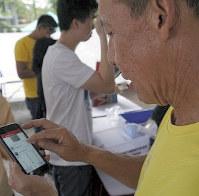 ジャカルタ特別州知事選の投票所で、スマートフォンを使って開票結果を入力・送信するボランティア=ジャカルタで2月15日、ジャカルタ支局助手エドナ・タリガン撮影