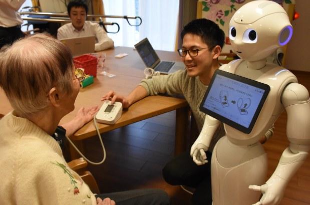 Pepperの指示に従って血圧を測る施設の利用者=静岡市駿河区のまごころタウン静岡で2016年11月16日、古川幸奈撮影