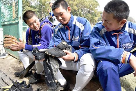 初戦に向け、試合用スパイクを磨きながら会話する神戸国際大付の(左から)田淵友二郎主将、谷口嘉紀選手、十河亮介選手=神戸市垂水区で、矢澤秀範撮影