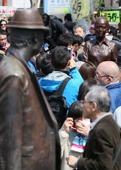 完成したさくらの銅像(中央奥)を見ようと集まった大勢の人たち。手前左は寅さんの銅像で、寅さんの視線の先で「お兄ちゃん」と呼びかけている設定になっている=東京都葛飾区柴又で2017年3月25日、佐々木順一撮影