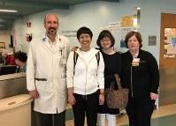 再会を喜ぶICUの担当医(左端)、看護師(右端)と記念撮影する柳恵子さん、母公子さん=2017年3月17日、家族提供