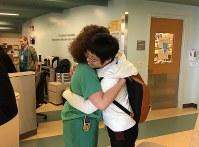 入院生活の大半を過ごしたICU(集中治療室)の前で、看護師から抱きしめられる柳恵子さん=2017年3月10日、家族提供