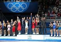 ソチ五輪フィギュアスケート団体で優勝し、表彰台の中央に上がり歓声に応えるロシアチーム。右端がプルシェンコ、右から4人目がリプニツカヤ。左は2位のカナダ、右は3位の米国=ロシア・ソチのアイスベルク・パレスで2014年2月9日、山本晋撮影