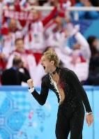 ソチ五輪フィギュアスケート団体で演技を終えてガッツポーズするプルシェンコ。奥は喜ぶロシアチーム=ロシア・ソチのアイスベルク・パレスで2014年2月6日、山本晋撮影