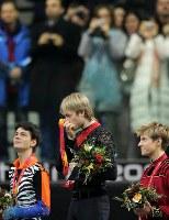 トリノ五輪フィギュアスケート男子シングルの表彰台で金メダルにキスするロシアのプルシェンコ(中央)。左は銀のランビール(スイス)、右は銅のバトル(カナダ)=パラベラ競技場で2006年2月16日、岩下幸一郎撮影