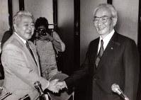オーナー会議でホークスの譲渡が正式に承認され、握手するダイエーの中内功会長兼社長(右)と南海電鉄の吉村茂夫社長=大阪市北区で1988年10月1日