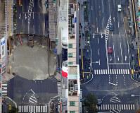 陥没していた現場(写真左)の舗装工事が完了し交通が再開された「はかた駅前通り」(同右)=福岡市博多区で(左)2016年11月8日午前9時42分、本社ヘリから須賀川理撮影(右)2016年11月15日午前8時46分、本社ヘリから矢頭智剛撮影
