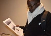 英文の「広島原爆アーカイブ」を紹介するチラシに見入るウガンダの外交官=米ニューヨークの国連本部で2017年3月30日、竹内麻子撮影