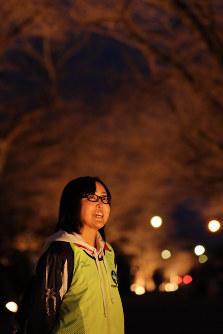 7年ぶりにライトアップされた夜の森の桜並木を見上げる佐藤香里さん=福島県富岡町で1日午後6時19分、喜屋武真之介撮影