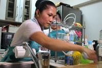 研修で利用者宅の台所を掃除するアミラさん=神奈川県内で年3月28日、中村かさね撮影