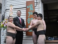 仮住まい先で弟子とともに握手する鳴戸親方(左から2人目)=東京都墨田区で2017年4月1日、飯山太郎撮影