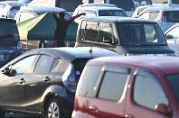 大勢の人たちが車中泊する「グランメッセ熊本」で車から降りて大きく伸びをする男性=熊本県益城町で2016年4月20日午前6時16分、久保玲撮影