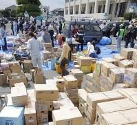 町役場の駐車場に積まれる集まった支援物資=熊本県益城町で2016年4月16日、三村政司撮影
