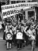 朝日訴訟を支援する関係者たちは1965年2月、東京都内で朝日さんの遺影を掲げて「訴訟を勝ちとる大行進」を行った。だが、最高裁大法廷は67年、国側勝訴の判決を下した