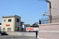 兵庫県警は今月3日に神戸山口組本部(右)の目の前に特別警戒所(左)を開設し、警戒や情報収集の体制を強化した=同県淡路市志筑で(一部画像を処理しています)