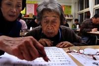 1990年、道内で初めて開かれた自主夜間中学。8年前から札幌市中央区の市立向陵中学校の教室で授業を始めた。英語の授業を受ける96歳の金井タマさん。「難しいねえ」とつぶやきながらもスタッフの阿部伸子さん(左)のアドバイスに熱心に聴き入っていた