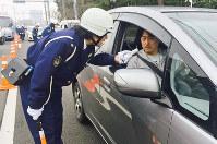 ドライバーに呼気検査を行う警察官=堺市西区で、宮嶋梓帆撮影