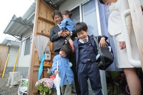 仮設住宅の自宅から入学式に向かうためランドセルを背負う権藤輝さん(右から2人目)=熊本県益城町で2017年4月11日午前8時38分、和田大典撮影