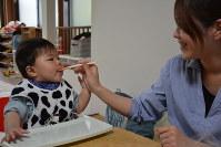 「おいしいね」と声をかけながら、生後8カ月の男児の口元に離乳食を運ぶ母親=稲田佳代撮影
