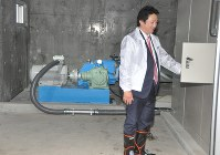 発電所内の発電機などについて説明する関係者