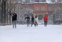 雪化粧された北海道庁前で帽子が飛ばされ追いかける観光客=札幌市中央区で2017年4月13日午後、梅村直承撮影