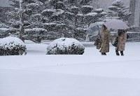 雪景色に変わった町中を歩く人たち=札幌市中央区で2017年4月13日午後、梅村直承撮影