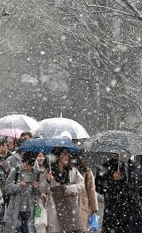 雪が舞う中、傘をさして歩く人たち=札幌市中央区で2017年4月13日午前8時45分、竹内幹撮影