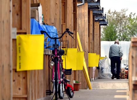 孤独死を防ぐために惣領仮設団地の玄関脇に掲げられた、無事を知らせる黄色い旗。旗が出たままで郵便物や新聞がたまるようなことがあれば、住民が町に通報する仕組みだ=熊本県益城町で2017年4月12日、野田武撮影