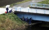 女児が遺体で発見された排水路に架かる橋の下付近を調べる捜査員=千葉県我孫子市で2017年3月26日午後0時34分、本社ヘリから宮武祐希撮影