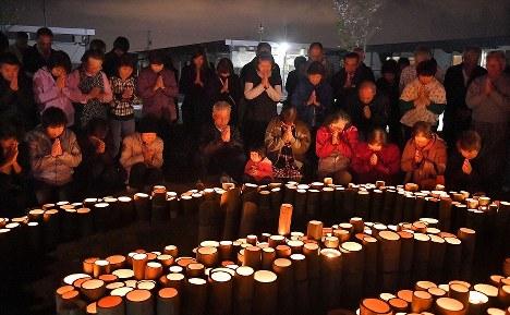 熊本地震前震の発生時刻に合わせ、竹灯籠に手を合わせる木山仮設団地の人たち=熊本県益城町で2017年4月14日午後9時26分、徳野仁子撮影