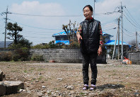 Takako Masuoka stands at the site of her home in Mashiki, Kumamoto Prefecture, which was destroyed in the April 2016 Kumamoto Earthquake, on March 28, 2017. (Mainichi)