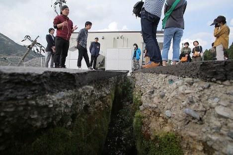 熊本地震で大きな被害が出た熊本県南阿蘇村で開かれた追悼イベントの合間に、「本震」による大きな亀裂が残るコンビニエンスストアで参加者に体験を語る東海大の学生で地震語り部の石田仁星(じんせ)さん(左)=熊本県南阿蘇村で2017年4月15日午後3時49分、和田大典撮影