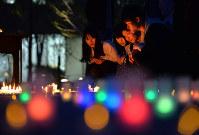 熊本地震の犠牲者を追悼する法要でキャンドルの灯を見つめる学生や職員=京都市北区の佛教大で2017年4月14日午後6時50分、小松雄介撮影