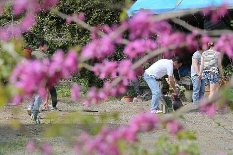 母を亡くした熊本地震の「本震」から1年となる16日、2月に解体した自宅を訪れ花を手向ける島崎浩さん(右から3人目)と家族=熊本県益城町で2017年4月16日午後3時9分、和田大典撮影