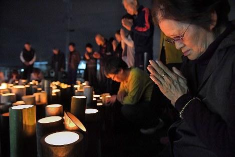 益城町の仮設住宅に置かれた竹灯籠の前で「本震」発生時刻にあわせ黙とうする古閑迫マキ子さん(70)(手前)。14日の「前震」発生時刻に続き、手を合わせた。姉の夫が1年前の4月16日、地震直後に亡くなった。「家が倒壊して避難所におり、葬式にも出られなかったことが悔やみ。家の解体もまだこれからという状態だが、今日は出てきてぜひ黙とうしたかった」と話した=熊本県益城町で2017年4月16日午前1時25分、和田大典撮影