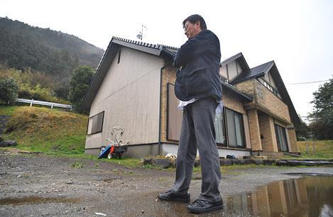 自宅前に立つ猿山さん。背後の山が土砂崩れを起こす危険があるため立野地区は地域全体での避難が続く=熊本県南阿蘇村で2017年4月8日、徳野仁子撮影.jpg