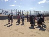 沖縄県名護市辺野戸のキャンプ・シュワブのフェンス前で現地コーディネーターの話を聞く学生たち=山田健太教授提供