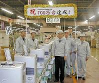 2001年12月、念願の年間生産台数100万台を達成した。右から5人目が吉井さん=新潟市の自社工場で