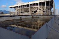 競泳会場(奥)に隣接する準備運動用のプールには汚水がたまり、蚊が大量発生していた=ブラジル・リオデジャネイロの五輪公園で2017年4月9日午後4時7分、朴鐘珠撮影