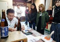 畑大治郎さん(左)からラベルの貼り方を教わる「19歳の酒」プロジェクトの参加者たち=滋賀県東近江市小脇町の畑酒造で、山本直撮影