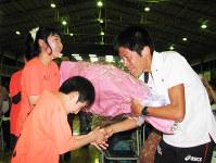 世界選手権に向けて地元の子供から激励の花束を贈られる川内優輝選手(右)=久喜市鷲宮の鷲宮中で