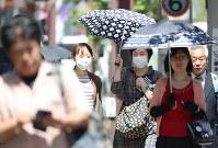 強い日差しを日傘で防ぎながら歩く女性たち=埼玉県熊谷市で2017年4月18日午後0時2分、小出洋平撮影