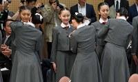 上級生(手前)に校章を付けてもらい、誇らしげな表情を見せる新入生=兵庫県宝塚市で2017年4月18日午前10時42分、平川義之撮影