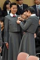 上級生(手前)に校章を付けてもらう新入生=兵庫県宝塚市で2017年4月18日午前10時42分、平川義之撮影