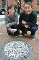 大阪城がデザインされたマンホールを見つけた池上和子さん(左)と修さん=大阪市北区で、倉田陶子撮影